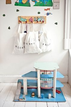 Hang tote bags from a wall coat rack. | 41 Clever Organizational Ideas For Your Child's Playroom