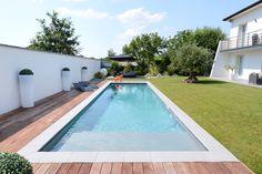 Jolie piscine rectangulaire, avec plage immergée et revêtement Crystalroc à base de cristaux de marbre.