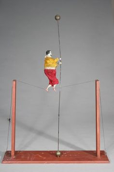 Clockwork Tightrope Walker / c.1885 / Ives, Blakeslee Company Bridgeport, Connecticut / extremely rare and graphic clockwork toy depicting a young man walking a tightrope. There are probably only 3 or 4 known examples of the toy; Material: Lead, Wood and Fabric