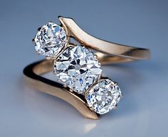 An Antique Bypass Diamond Engagement Ring, Circa 1915. The 14K rose gold ring features three sparkling antique cushion cut diamonds, ~2.03 carats.