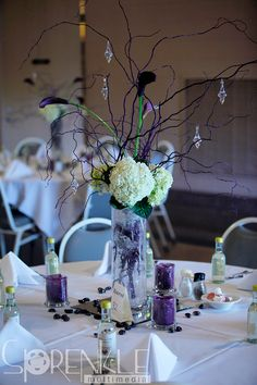 Table arrangement with white hydrangeas and purple orchids in a tall vase, purple twigs strung with glass jewelry, purple candles with marbles with mini personalized wine bottles