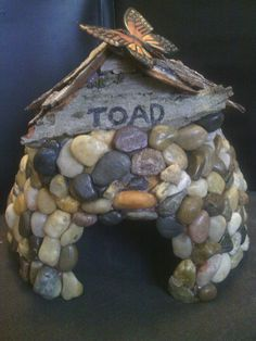 A DIY toad house made with a thrift-store terracotta pot turned upside down and Dollar Tree pebbles hot-glued on. The roof is made from a fallen piece of old tree bark found alongside the road. Put soil and live moss from the yard under the roof. Frog House, Toad House, Gnome House, Garden Yard Ideas, Garden Crafts, Garden Projects, Projects To Try, Garden Fun, Gnome Garden