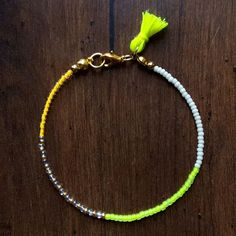 Radiate bohemian vibes with this awesome seed bead bracelet! Created with glass seed beads in neon yellow, tangerine, cream, and gold; a bright + tiny tassel; and finished with a dainty little gold lo