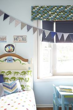This Emily Henderson designed boy's room features dark navy shades topped with a colorful, geometric valance from Décorview.