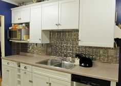 """A project actually completed rather than just pinned! -- a new kitchen backsplash using the Fasade Thermoplastic panels (brushed nickel finish) that imitate pressed tin.  Couldn't afford a celebrity for the """"after"""" photo, so the cat stood in for one."""