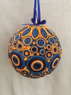 2 1/2 foam ball covered in paper quilled design. Colors are Two different blues and orange with a blue ribbon to hang it.