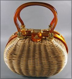 """A UNIQUE oval shaped vinyl rattan purse from the 70's. The frame and handle highlights the unique shape with gold swirled Lucite. The interior is lined with spill proof plush-colored vinyl with a zippered sidewall pocket. Designed by """"Tropic of Miami""""."""