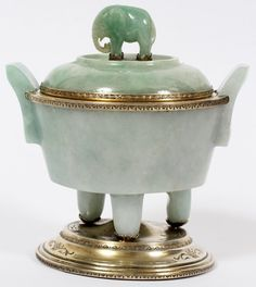 """EDWARD I. FARMER STERLING & CHINESE JADE COVERED URN-FORM INKWELL, EARLY 20TH C., H 5"""", W 5"""":Antique light green jade urn flanked by handles, having a hinged cover with standing elephant finial, sterling silver mounts, stamped underneath """"Edward I. Farmer, New York""""). The hinged cover opens to a removable sterling silver insert. Measures H.5 1/4"""", W.5""""."""
