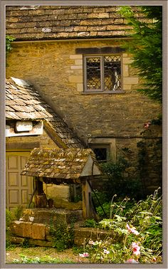 Old house with water well in Bibury, Gloucestershire