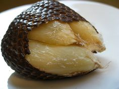 """""""SALAK""""....The fruit of the salak tree grows in clusters at the base of the short-stemmed palm, and is also known as """"snakeskin fruit,"""" due to its scaly appearance. Peel it by pinching the tip and pulling away the skin to reveal three large lobes containing inedible pits. The edible flesh tastes sweet and acidic, with a dry, crunchy texture. But beware: a careless peeler can cut a finger on the sharp scales."""