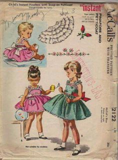 1950s sewing pattern little girl's pinafore with snap-on petticoat and rosebud embroidery transfer.
