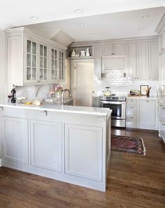 Fabulous kitchen features gray shaker cabinets paired with marble countertops and subway tile backsplash.