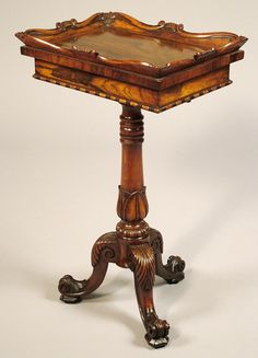 *A Late Georgian Jardiniere in the Manner of Gillow. Constructed of well figured Rosewood, rising from tripod scrolled feet, in the Grecian taste, a lotus leaf and ring turned central stem; the jardinière of spring released lid form, and having a moulded octagonal top, with bead and reel decoration. Circa 1825.