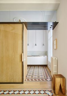Contemporary oak cabinetry features alongside original patterned tiles in this 19th-century Barcelona apartment