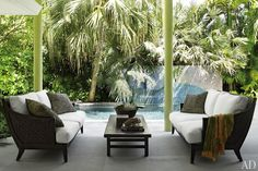 A terrace features vintage McGuire sofas with cushions upholstered in a Sunbrella fabric and pillows clad in a Donghia jacquard; the pool area's mosaic mural is by artist Debra Yates.