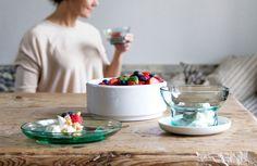 Bord en schaal met fruit op een houten tafel; op de achtergrond een vrouw met een schaaltje in de handen