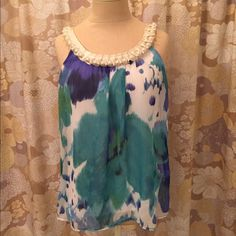 """Beautiful Watercolor Tank Top With Pearls & Bow Absolutely gorgeous this top has blues, greens, cream and white in it.  The neckline boasts faux pearls and a cream ribbon that ties into a pretty bow in the back.  The top layer is sheer but there is a white tank top built into the shirt.  I was trimming threads and accidentally made a small cut on the tank top underneath.  It is very small (.25"""") and has been repaired.  It can not been seen when worn.  100% Polyester.  Hand wash cold and line…"""