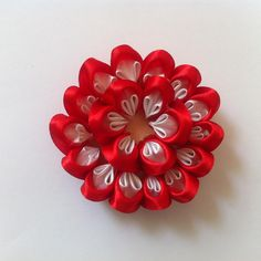 I simply adore Kanzashi flowers.  They are just beautiful.  Here is how to make this gorgeous Kanzashi bloom.  Then use the flower to craft beautiful hair clip or headband, corsage, brooch, etc..     Materials   	satin ribbon 	bead 	thread and needle 	scissors 	fabric glue / hot glue