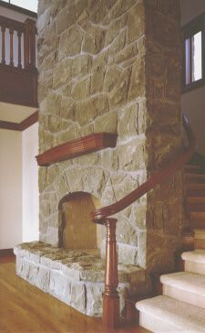 A cozy fireplace with stairs wrapped around it.