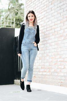 Look do dia por Jess Vieira com macacão jeans de lavagem clara, blusa de manga longa listrada, cardigã preto e botinha de cano médio.