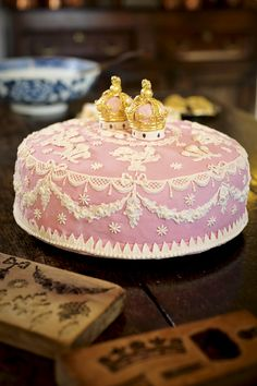 A traditional English 'Twelfth Cake'. Served on Epiphany and intricately iced with two gilded sugar crowns, symbolizing the king and queen of the evening's revels.