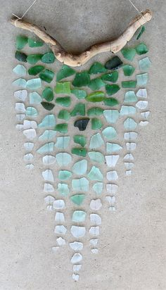 Seaglass windchime DIY instructions:\n Lay out the seaglass by color in ombre.\n Attach the string to the driftwood branch to form a hanger, tie knots and dab a bit of glue to ensure a tight hold.\n String the seaglass together with the craft wire, from light to dark pieces will give you the ombre effect.\n Last step to create your ocean art is to attach the seaglass strands to the driftwood branch and viola you have made a beautiful masterpiece.