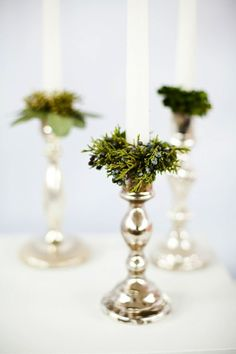 Christmas Decorations -Bring the evergreen indoors! Spice up your classic silver candlesticks with a small circle of greenery at the base of the candle. Bonus points if you use candles in one of these punchy colors!