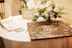 guests signed a varnish wood sign in white ink to congratulate the bride and groom. a low lush arrangement of white garden roses, white ranunculus,white larkspur, white spray roses, dusty miller, button chamomile, white tulips, silver dollar eucalyptus, white stock and orlaya lace in a gold compote.