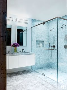 Fixtures by Remains Lighting crown Barbara Barry mirrors for Kallista in the master bath of Will Ferrell's Manhattan apartment, which was decorated by Shawn Henderson Interior Design; the sink and shower fittings are by Hansgrohe.