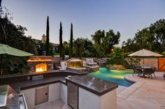 Sharp cuts and modern architectural designs. A pool brought to life by a warm and inviting fireplace, low dim lighted waterfall, and custom built bbq with marble polished countertops.   The backyard furniture fit the design style and decor of this backyard just right.