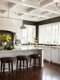 A bright kitchen decorated with coffered ceilings, creamy cabinets & chocolate brown bar stools