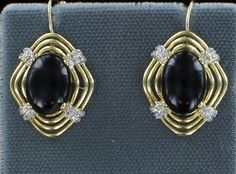 Southern Classic Jewelry - USA Period: 1960 Material: 14KT YELLOW GOLD Stones: ONYX AND .50 CT TW DIAMONDS Condition: 3 LAYERS OF 14KT YELLOW GOLD WIRE CREATE THE DIAMOND SHAPE OF THESE UNUSUAL EARRINGS. AN OVAL BLACK ONYX IS SET IN THE CENTER OF THE GOLD FRAME WHICH IS COMPLETED BY 4 BANDS OF DIAMONDS ON EACH EARRING, .50 CT TW. THESE STUNNING EARRINGS ARE ON A WIRE AND HAVE A HANGING LENGTH OF 1 1/4 INCH. $595.00