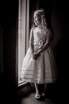Ray Lockyer Yeovil Wedding Photographer - A Flower Girl takes a glance out of a window at Haselbury Mill