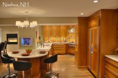 Shaker Kitchen- This photo focuses on the kitchen area adjacent to the full bar area to the far left, Decorative door panels on built in Refrigerator, counter height seating, shaker style cabinets, caeser stone counter tops