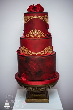 'Melisandre' - based on the character from 'Game of Thrones' Wedding cake ~  Melisandre is a dark character, known as the Red Priestess, she claims to know magic and have powers of prophecy. Airbrushed red to create a dark mottled effect with the base tier over painted with black to make it more 'stormy', accented with gold cake lace, black pearls and deep red roses with falling petals