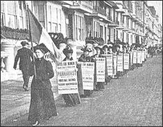 Suffragettes march with placards adorned with slogans for the women's vote