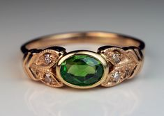 A Vintage Demantoid Engagement Ring The 14K rose gold ring is centered with a bezel-set Russian demantoid flanked by two pairs of stylized leaves embellish