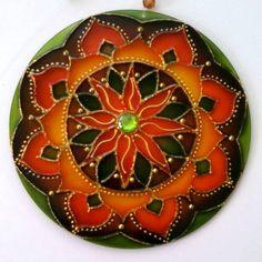 Mandalas em acrílico de 15cm de diâmetro, pintura vitral, decoradas com tinta relevo dourada e pedrinhas coloridas em ambos os lados. R$ 27,00