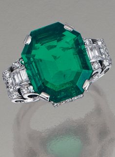 EMERALD AND DIAMOND RING, CIRCA 1935 Centring on an octagonal step-cut emerald weighing 7.77 carats, embellished by stylised scrolls elements set with single-cut and baguette diamonds, size 55.