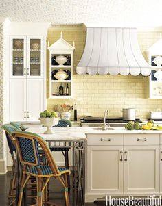 So cute - your own little bistro! From House Beautiful: Designer John Oetgen spent a lot of time in French brasseries, which inspired this amusing kitchen complete with blue-and-green bistro stools. The range hood, done in hand-hammered zinc, was made to look like a fabric canopy.