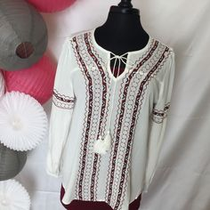 Long Sleeve with elastic, white woven top with burgundy accents. This cute shirt has tie tassel neck and beautiful front embroidery. Perfect for fall, winter, or spring. We have it paired with our Bur