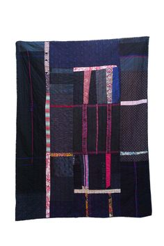 OMNI QUILT - Made from cotton, silk, wool and polyester sourced in the USA, Myanmar, Laos, Cambodia and France.  This quilt features two very unique textiles sourced in Myanmar: the centerpiece, a section of a jacket made by the Chin people, no longer being made in the same way today; and a wool tunic worn by the Pa-Oh women of Inle Lake, black with pink detail stitching.