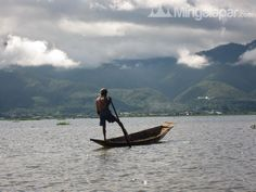 A fisherman paddling with his leg in Myanmar