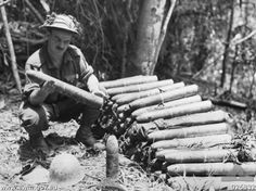 An Australian soldier inspects Japanese artillery rounds abandoned at Ioribaiwa. These rounds had been carried the length of the track by Japanese soldiers.