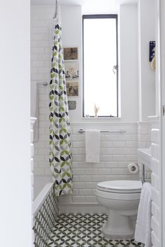 tiny bathroom with concrete and bricks walls in white wall mounted toilet in white white bathtub with pattern on its walls multicolored shower curtain multicolored ceramic floors of Great Choices of Fancy Colors for A Small Bathroom