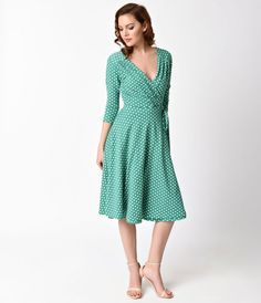 Oh, the dotted divinity, gals! Allow us to present The Kelsie Dress, a fabulous green wrap dress in a delightful white polka dot print throughout. Crafted from an exceptionally soft quality stretch knit blend, this stupendous swing blends all the right 50