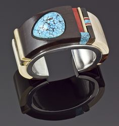 Cuff | Edison Cummings.  Sterling silver inlayed with fossil ivory, ironwood, coral and turquoise.