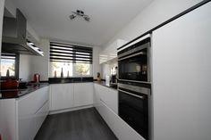 Witte hoogglans greeploze keuken met zwart gepolijst composieten werkblad — in Schiedam.