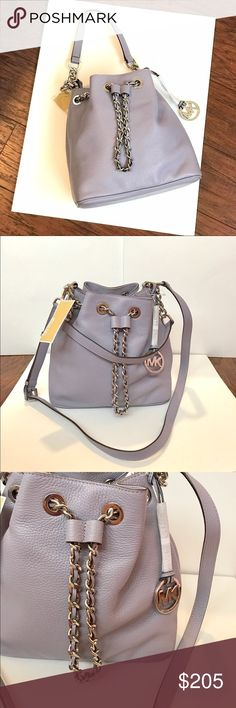 """MICHAEL KORS Frankie Md Drawstring Messenger Guaranteed Authentic! Beautiful Michael Kors Frankie medium drawstring messenger in pebble leather. Color: Lilac and silver tone hardware. Magnetic snap and drawstring closure in silver chain and leather combination. MK logo charm. Shoulder strap in chain and leather with 9"""" drop. Adjustable and removable crossbody strap with max. 24"""" drop. 1 interior zip pocket, and 4 slid open pockets. Measurements: Item will be videotaped prior to shipping to…"""