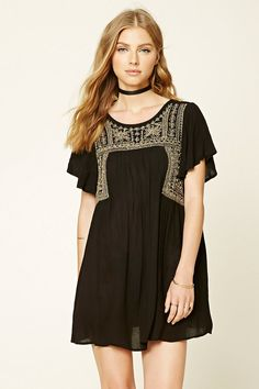 A woven gauze peasant dress featuring a metallic embroidered front, V-cut back, short sleeves, and a round neckline.